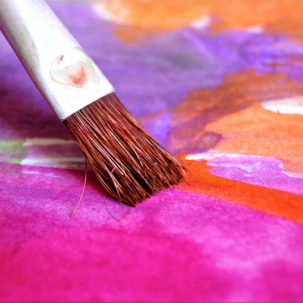 close up of a paintbrush on a pink and purple watercolour canvas