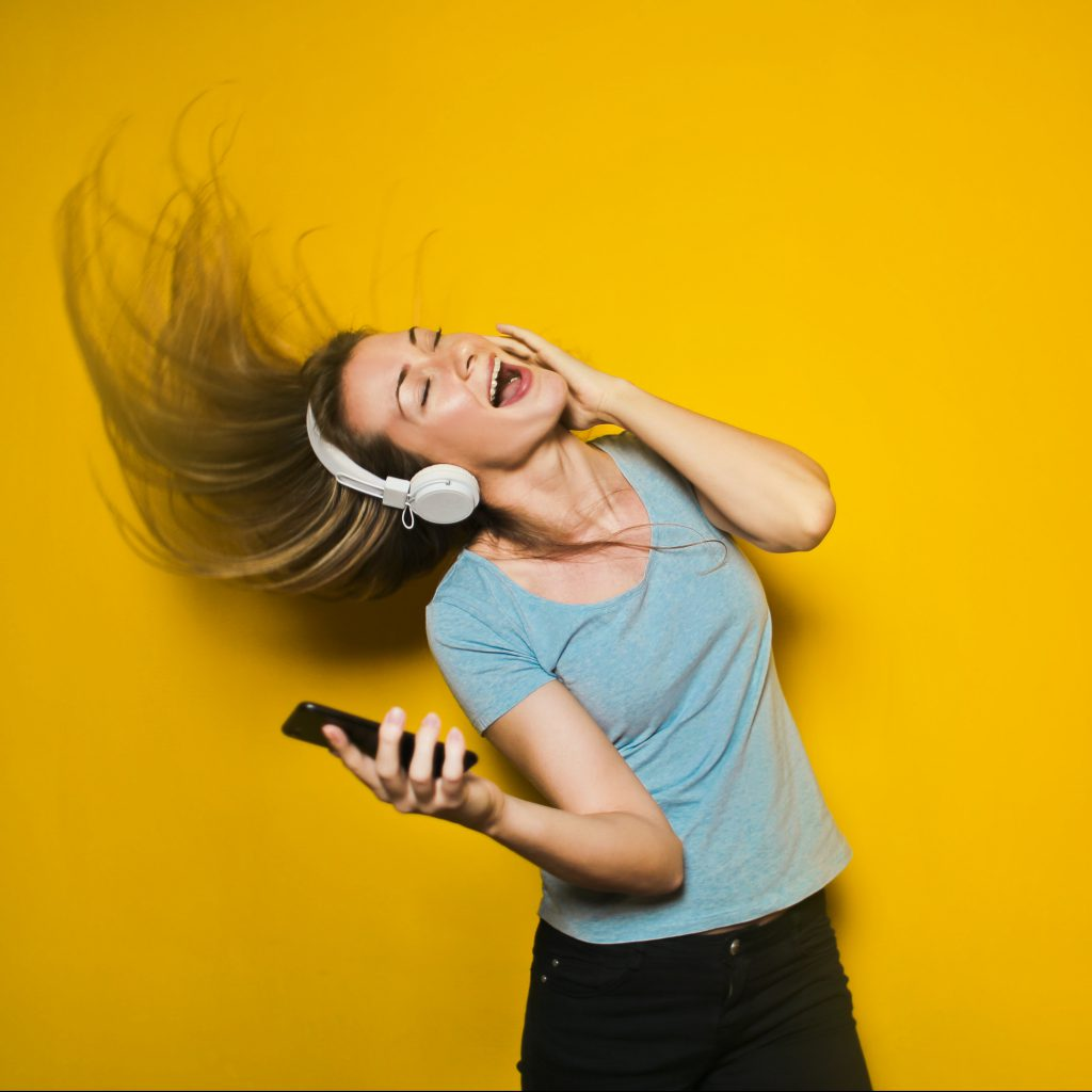 woman listening to music from a phone through wireless headphones