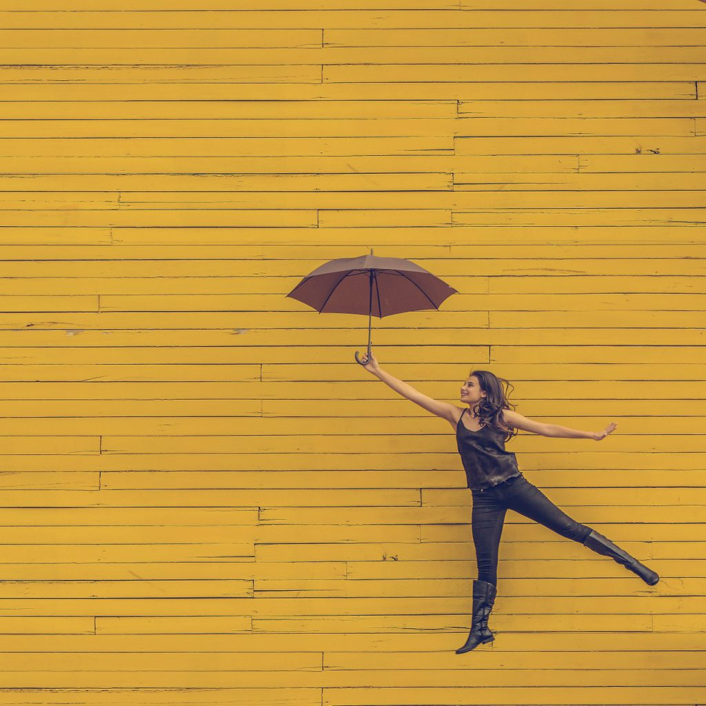 woman floating with a red umbrella in front of a yellow wall background
